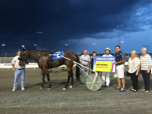 Jim Huck presents Rod Hughes with the congratulatory sign from Kawartha Downs.